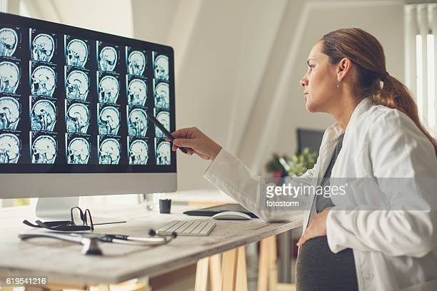 Pregnant female doctor examining brain scan