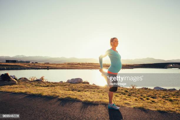 pregnant female runner stretches on a trail at sunset - pregnant stock pictures, royalty-free photos & images