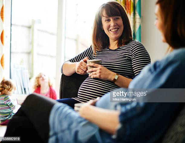Pregnant friends at home, laughing together