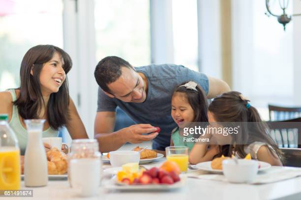 Pregnant Hawaiian Couple and Young Daughter eating dinner at table