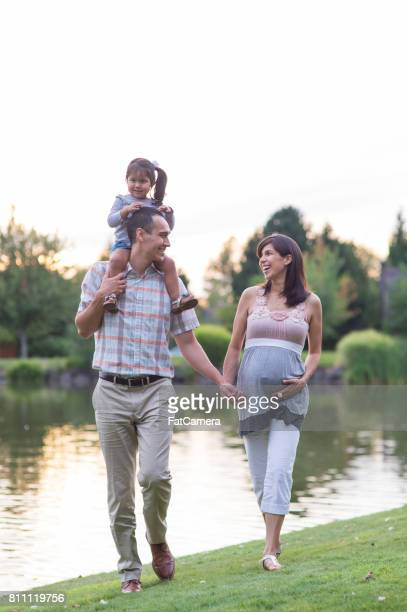 pregnant hawaiian couple and young daughter in park outdoors - fat belly girl stock photos and pictures