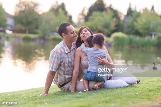 Gravida Hawaiian par och unga dotter i Park utomhus