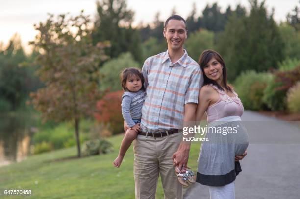 Gravida Hawaiian par Snuggling i Park utomhus med unga dotter