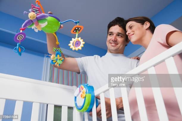 Pregnant Hispanic couple holding mobile over crib