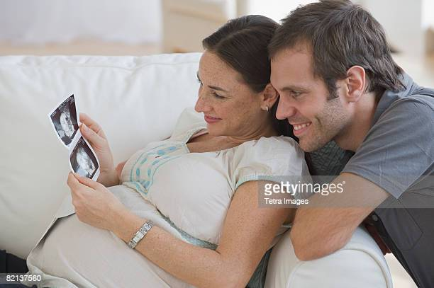 Pregnant Hispanic couple looking at ultrasound printout