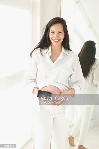 Pregnant Hispanic woman holding cell phone