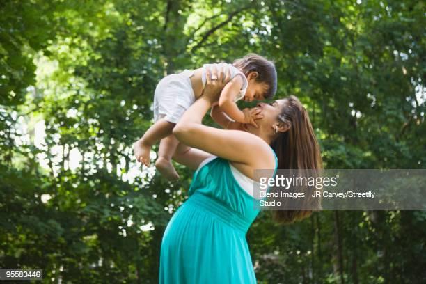 Pregnant Hispanic woman lifting baby boy