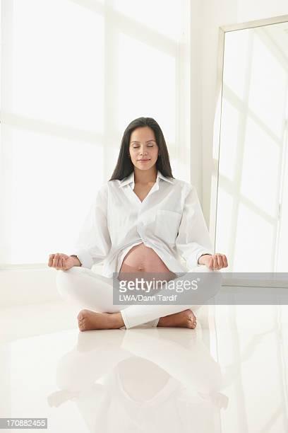 Pregnant Hispanic woman meditating