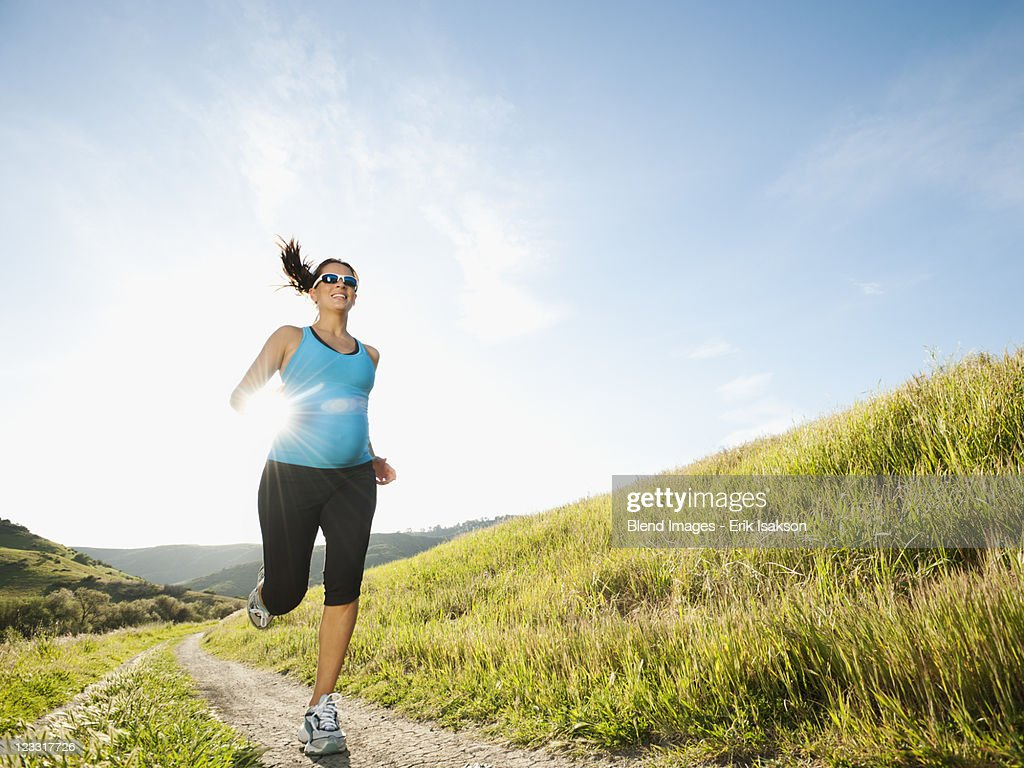 Pregnant Hispanic woman running in remote area : Stock Photo