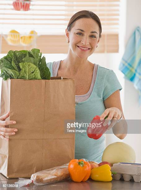 Pregnant Hispanic woman unpacking groceries