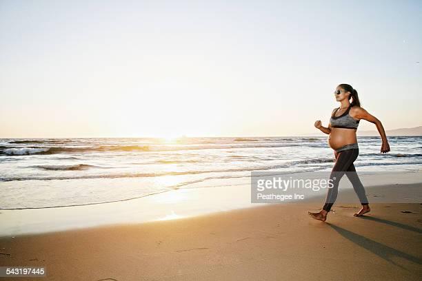 Pregnant Hispanic woman walking on beach