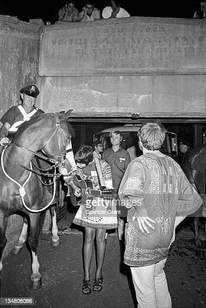 A pregnant Joan Baez serenades a cop's horse at Harvard Stadium Brighton Boston Massachusetts 1969