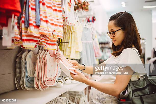 Pregnant lady shopping for baby items joyfully