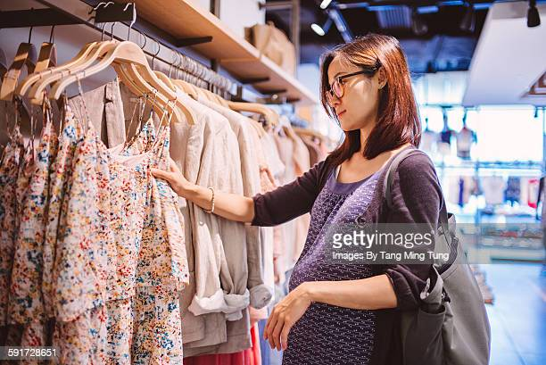 pregnant lady shopping for clothing in a boutique - mid adult woman sweater stock pictures, royalty-free photos & images