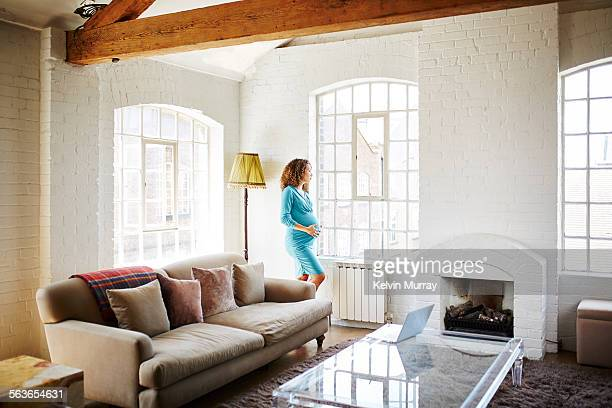 Pregnant lady stands by a window in her apartment