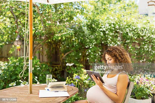 Pregnant lady uses tablet whilst sitting in garden