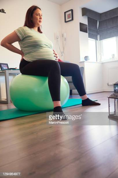 pregnant lady with sore back - human back stock pictures, royalty-free photos & images
