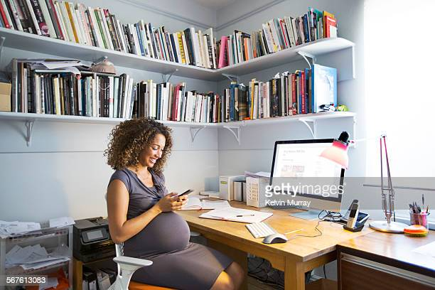 pregnant lady works from her home office - receiving stock pictures, royalty-free photos & images