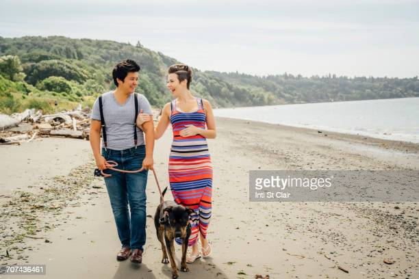 pregnant lesbian couple walking dog on beach - mid adult stock pictures, royalty-free photos & images