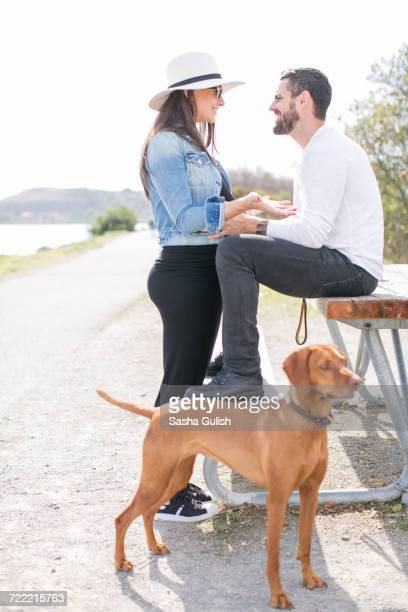 Pregnant mature couple having discussion at park bench on coast