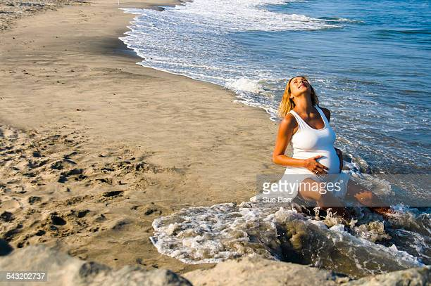 Pregnant mature woman sitting in ocean waves on beach whilst touching stomach