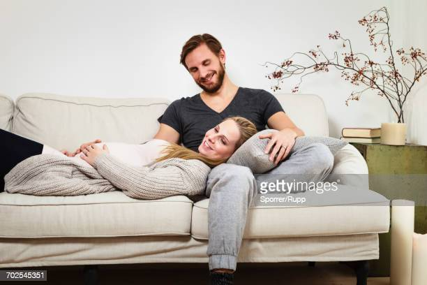 pregnant mid adult couple relaxing on sofa - jogging pants stock pictures, royalty-free photos & images