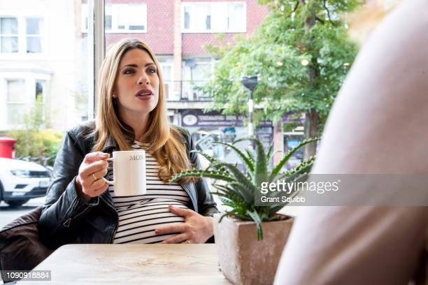 pregnant mid adult woman chatting with friend in cafe - pregnant coffee stock pictures, royalty-free photos & images
