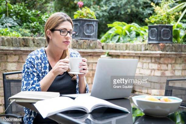 pregnant mid adult woman looking at laptop on patio table - cardigan sweater stock pictures, royalty-free photos & images