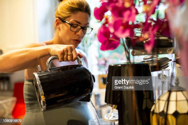 Pregnant mid adult woman making a drink in kitchen