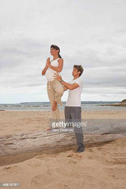 Pregnant mid adult woman with personal trainer practicing yoga at beach