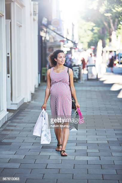 Pregnant mixed race lady walks with shopping