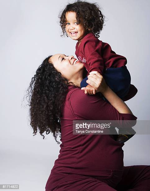 pregnant mixed race mother hugging son - mixed wrestling stock pictures, royalty-free photos & images