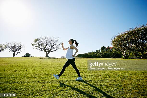 Pregnant mixed race woman exercising in field