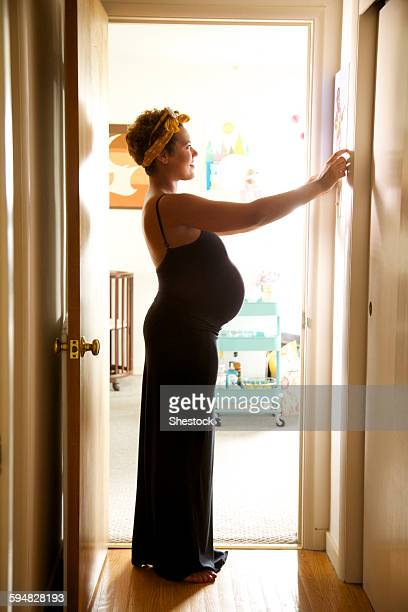 pregnant mixed race woman hanging picture - embarazada fotos fotografías e imágenes de stock