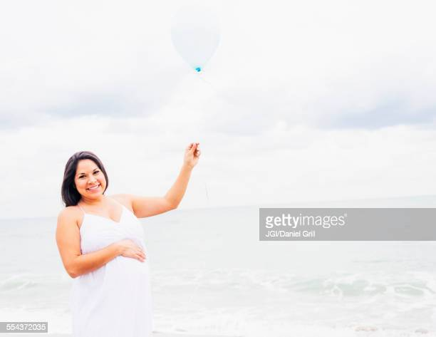 Pregnant mixed race woman holding balloon on beach