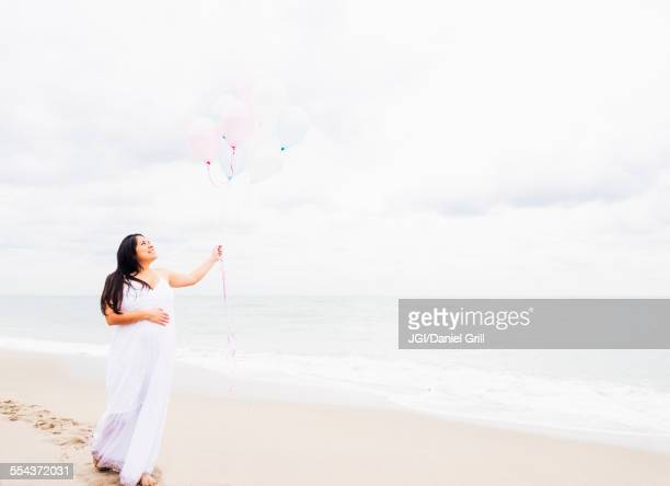 Pregnant mixed race woman holding balloons on beach