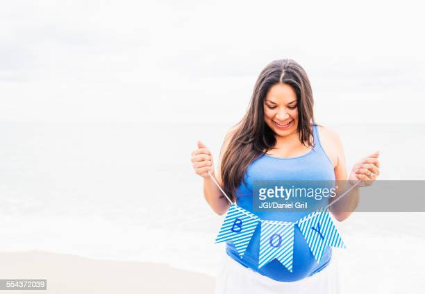 Pregnant mixed race woman holding boy banner on beach