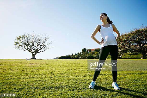 Pregnant mixed race woman standing in field