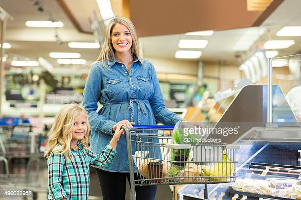 Pregnant mom and young daughter shopping in grocery store