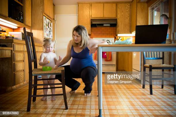 Pregnant mom squats near toddler in kitchen