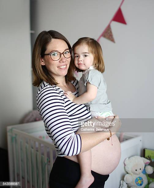 a pregnant mom with her 2 years old girl - 30 34 years stock-fotos und bilder