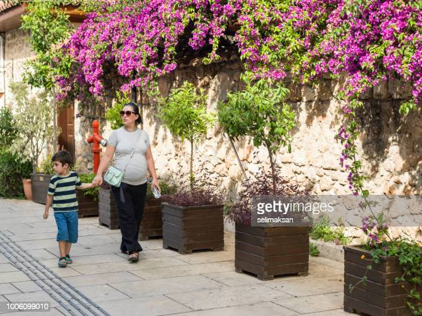 Pregnant Mother And 5 Years Old Son Walking In By Bougainvillea Wall
