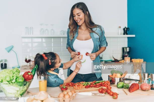 pregnant mother and daughter making vegetable smiley face - stomach stock pictures, royalty-free photos & images