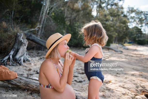 pregnant mother and daughter on beach at sunset - beautiful beach babes stock pictures, royalty-free photos & images
