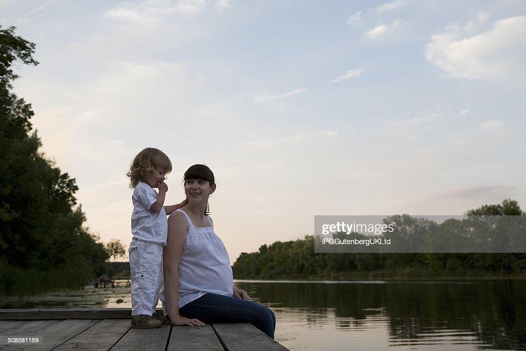 妊娠の母と娘に座った桟橋 : ストックフォト