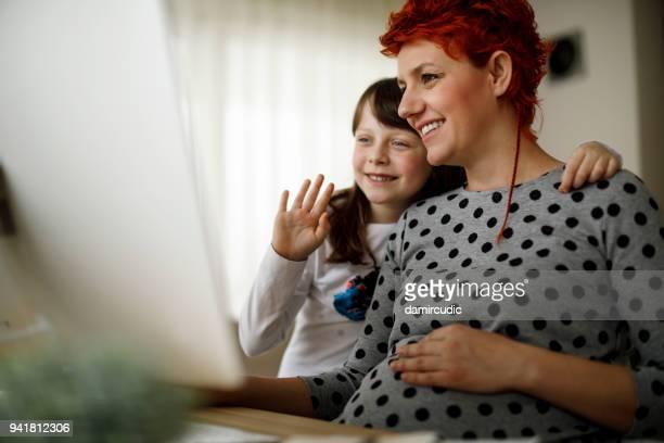 schwangere mutter und tochter wird mit vater - mother daughter webcam stock-fotos und bilder