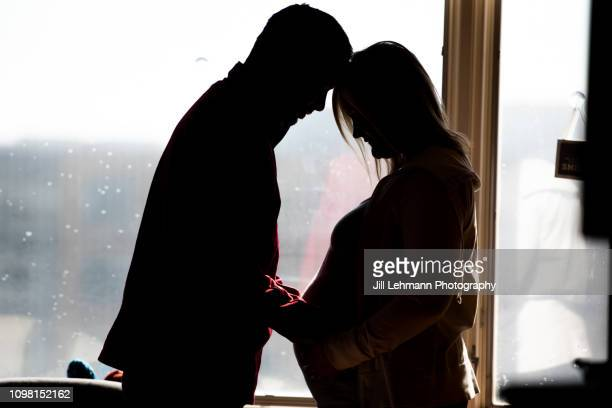 pregnant mother and father of twins in hospital room stand in silhouette shot - husband stock pictures, royalty-free photos & images