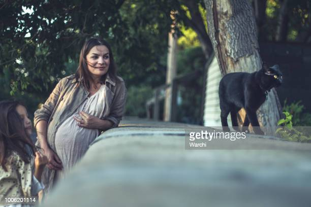 Pregnant mother and her daughter admiring a black cat