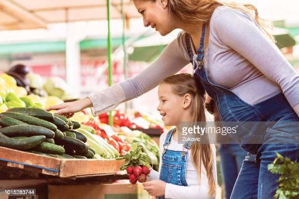 pregnant mother and her daughter buying vegetables - mercato di prodotti agricoli foto e immagini stock