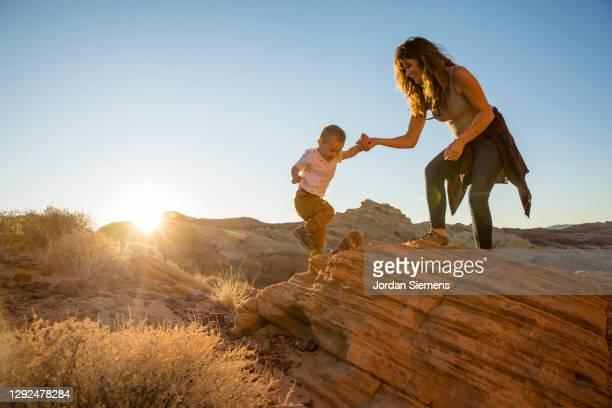 a pregnant mother and her son hiking in the desert. - erwachsener über 30 stock-fotos und bilder